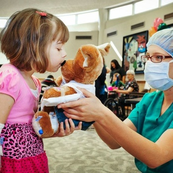 Small patient madeline smith 10 gives her teddy bear a kiss before it is taken in for surgery by child life fellow leah dunn 162316